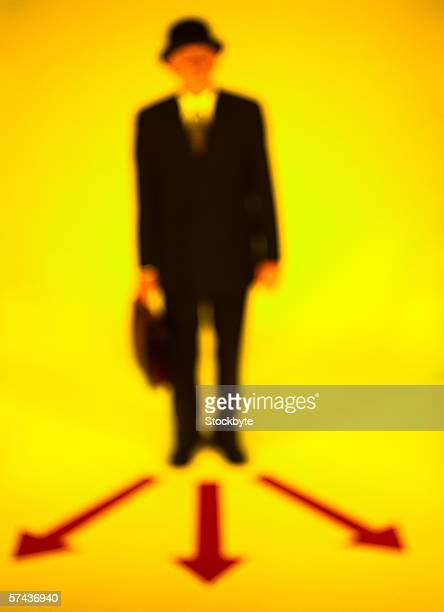 toned blurred view of a businessman standing on an array of three arrows