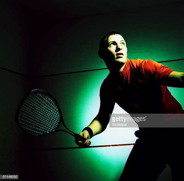 toned low angle close-up of a man hitting a shot in a game of tennis