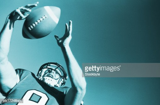 toned low angle view of a football player catching the ball : Stock Photo