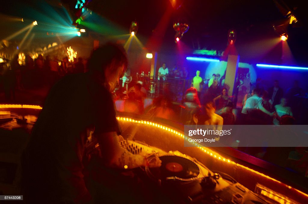 toned shot of a disc jockey playing music and people dancing in a discotheque : Stock Photo
