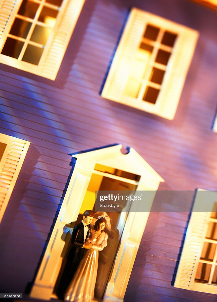 toned shot of bride and groom figures standing in the doorway of a miniature house : Stock Photo