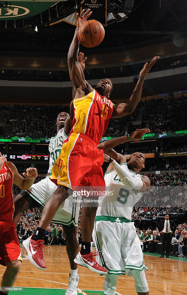 Toney Douglas #15 of the Houston Rockets goes up for a rebound against Brandon Bass #30 and Rajon Rondo #9 of the Boston Celtics on January 11, 2013 at the TD Garden in Boston, Massachusetts.
