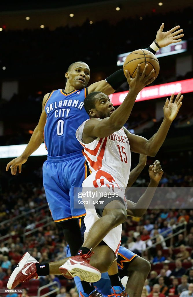 Toney Douglas #15 of the Houston Rockets takes a shot against Russell Westbrook #0 of the Oklahoma City Thunder at the Toyota Center on December 29, 2012 in Houston, Texas.