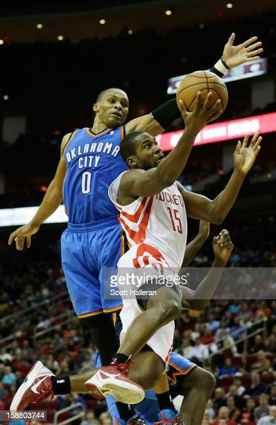 Toney Douglas of the Houston Rockets takes a shot against Russell Westbrook of the Oklahoma City Thunder at the Toyota Center on December 29 2012 in...