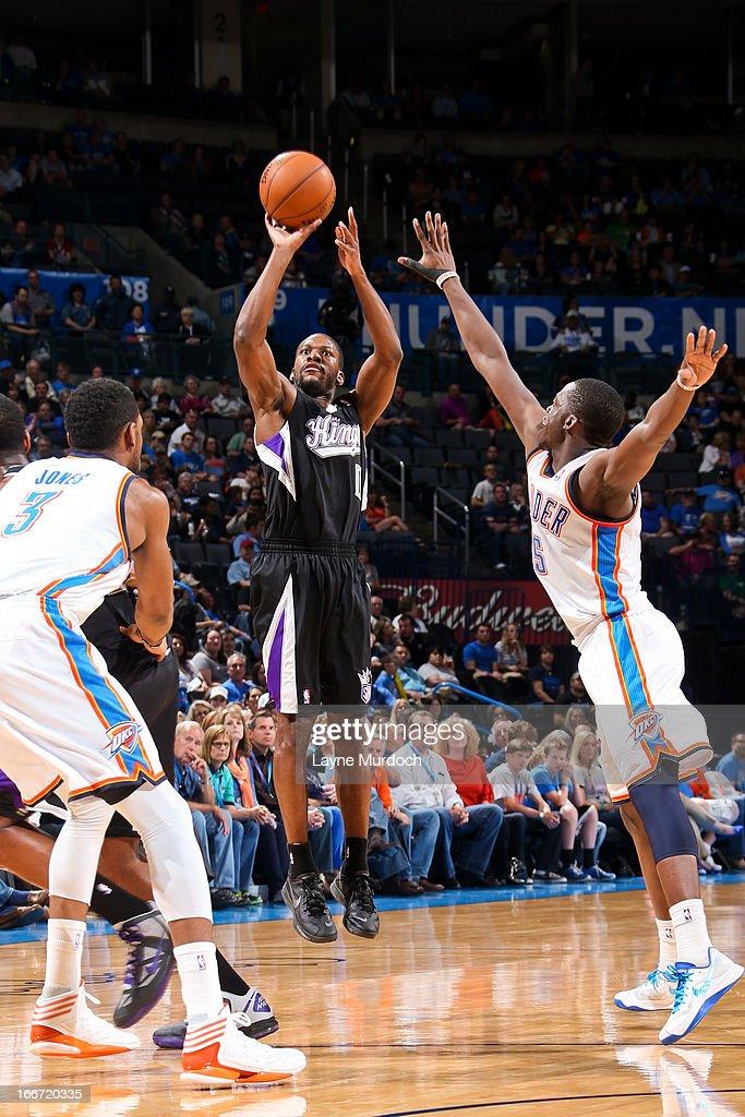 Toney Douglas #0 of the Sacramento Kings shoots a three-pointer against Reggie Jackson #15 of the Oklahoma City Thunder on April 15, 2013 at the Chesapeake Energy Arena in Oklahoma City, Oklahoma.