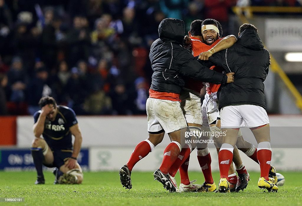 Tonga players celebrate at the final whistle during the International rugby union test match between Scotland and Tonga at Pittodrie in Aberdeen on November 24, 2012. Tonga beat Scotland 21-15.