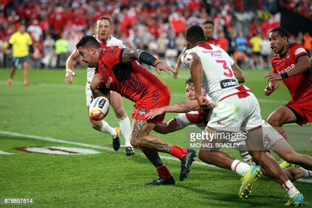 Tonga's Andrew Fifita loses the ball after being tackled during the Rugby League World Cup men's semifinal match between Tonga and England at Mt...