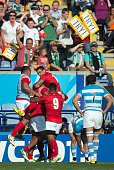 Tonga's prop Soane Tonga'uiha celebrates with teammates after scoring a try during a Pool C match of the 2015 Rugby World Cup between Argentina and...
