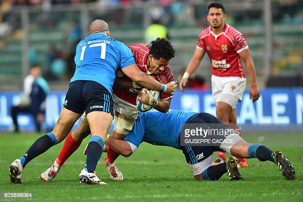 Tonga's Valentino Mapapalangi is tackled by Italy's Nicola Quaglio and Simone Ferrari during the rugby union Test match between Italy and Tonga at...