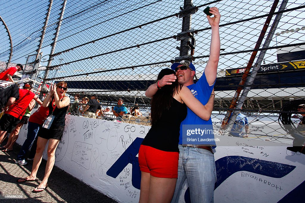 Toni Cianfrocco (L), of Washington D.C., and Greg Stevens celebrate their engagement on the start finish line prior to the NASCAR Sprint Cup Series Toyota Owners 400 at Richmond International Raceway on April 26, 2014 in Richmond, Virginia.