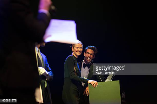 Toni Garrn and Jon Kortajaren appear on stage during the amfAR Milano 2014 Gala Dinner and Auction as part of Milan Fashion Week Womenswear...