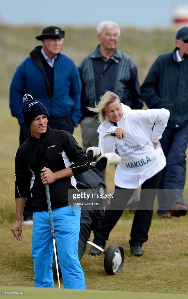 Toni Hakula of Finland plays his third shot on the 7th hole during the afternoon round watched by his mother Helena Hakula in the final of the 2013 Amateur Championship at Royal Cinque Ports Golf Club on June 22, 2013 in Deal, England.