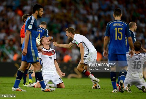 Toni Kroos and players of Germany celebrate while Argentina players show dejection after the 2014 FIFA World Cup Brazil Final match between Germany...