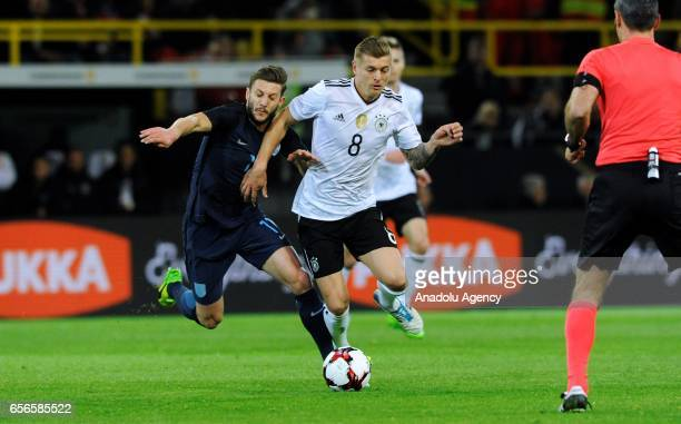 Toni Kroos of Germany and Adam Lallana of England in action during friendly soccer match between Germany and England at the SignalIduna Park in...
