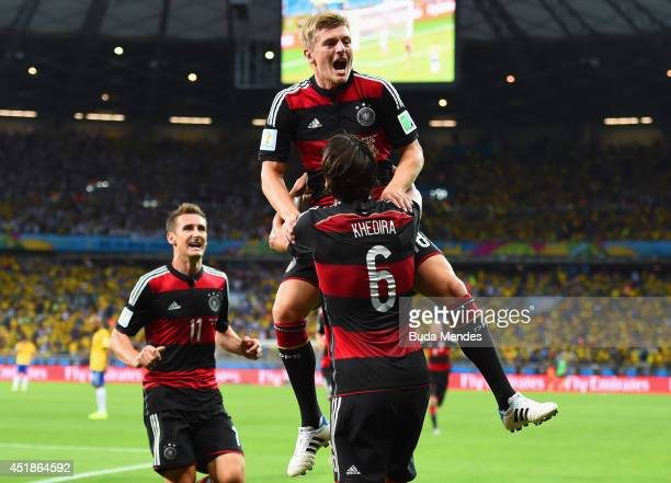 Toni Kroos of Germany celebrates scoring his team's fourth goal with teammates Miroslav Klose and Sami Khedira during the 2014 FIFA World Cup Brazil...
