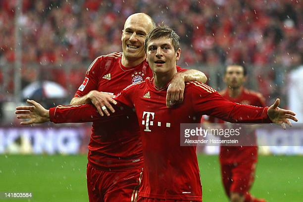 Toni Kroos of Muenchen celebrates scoring the opening goal with his team mate Arjen Robben during the Bundesliga match between FC Bayern Muenchen and...