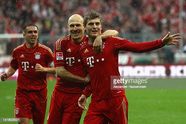 Toni Kroos of Muenchen celebrates scoring the opening goal with his team mate Arjen Robben and Philipp Lahm during the Bundesliga match between FC...