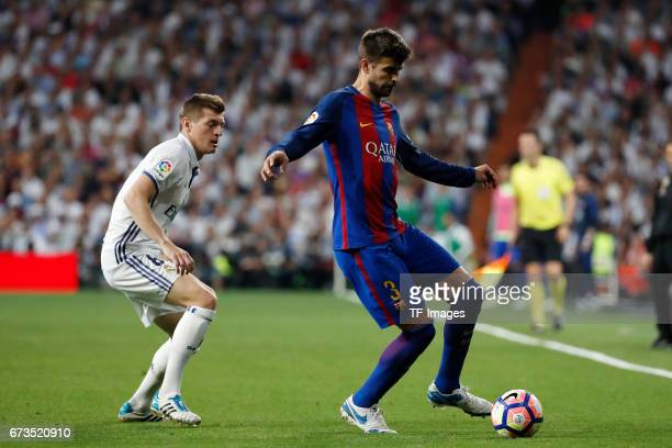 Toni Kroos of Real Madrid and Gerard Pique of FC Barcelona battle for the ball during the La Liga match between Real Madrid CF and FC Barcelona at...