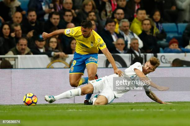 Toni Kroos of Real Madrid and Jonathan Calleri of Las Palmas compete for the ball during the La Liga match between Real Madrid and Las Palmas at...