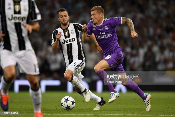 Toni Kroos of Real Madrid and Miralem Pjanic of Juventus compete for the ball during the UEFA Champions League final match between Juventus and Real...