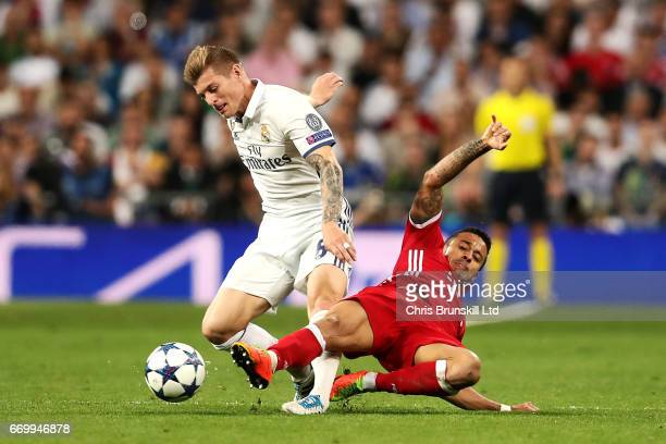 Toni Kroos of Real Madrid CF is tackled by Thiago Alcantra of FC Bayern Muenchen during the UEFA Champions League Quarter Final second leg match...