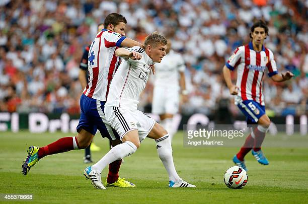 Toni Kroos of Real Madrid competes for the ball with Gabi Fernandez of Atletico de Madrid during the La Liga match between Real Madrid CF and Club...