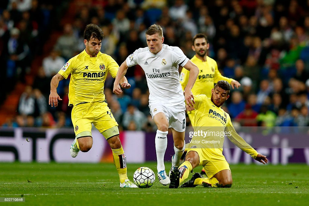Toni Kroos of Real Madrid competes for the ball with Jonathan dos Santos (R) and Manuel Trigueros of Villarreal during the La Liga match between Real Madrid CF and Villarreal CF at Estadio Santiago Bernabeu on April 20, 2016 in Madrid, Spain.