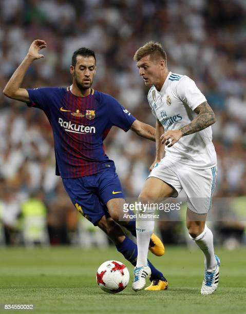 Toni Kroos of Real Madrid competes for the ball with Sergio Busquets of FC Barcelona during the Supercopa de Espana Final second leg match between...