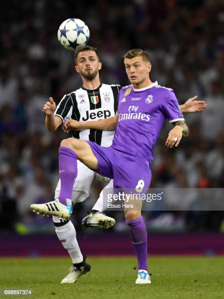 Toni Kroos of Real Madrid controls the ball under pressure of Miralem Pjanic of Juventus during the UEFA Champions League final match between...