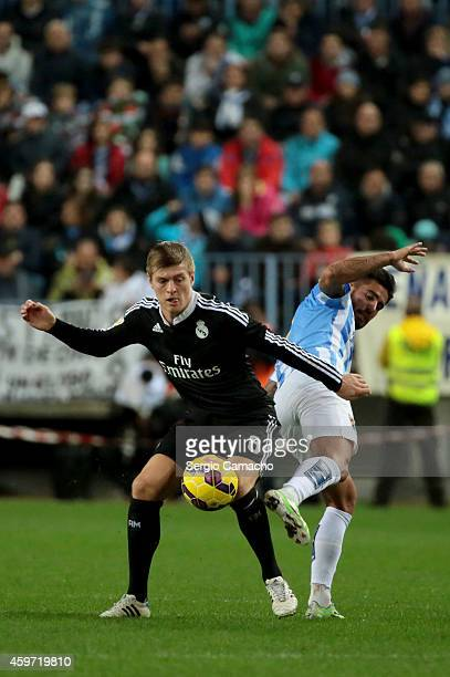Toni Kroos of Real Madrid duels for the ball with Samuel Garcia of Malaga CF during the La Liga match between Malaga CF and Real Madrid CF at La...