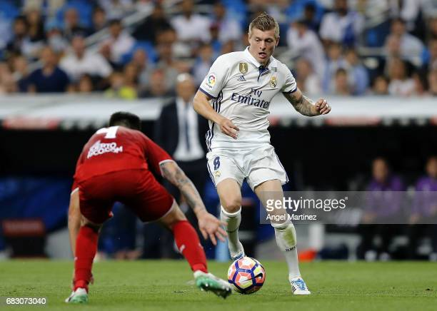 Toni Kroos of Real Madrid is challenged by Matias Kranevitter of Sevilla FC during the La Liga match between Real Madrid and Sevilla FC at Estadio...