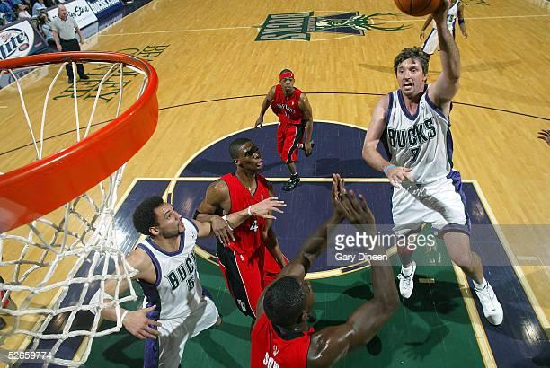 Toni Kukoc of the Milwaukee Bucks shoots against Pape Sow of the Toronto Raptors as Dan Gadzuric of the Milwaukee Bucks Chris Bosh and Rafer Alston...
