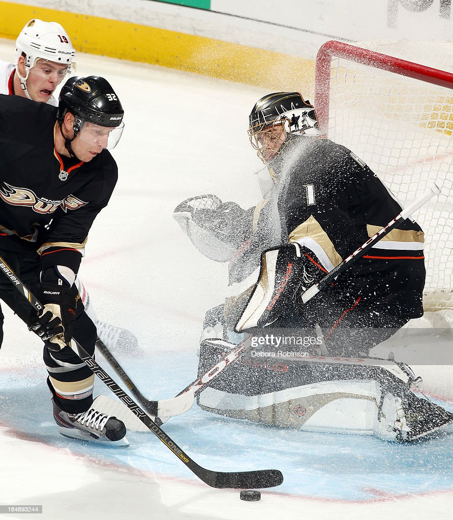 Toni Lydman #32 and Jonas Hiller #1 of the Anaheim Ducks battle for the puck against Jonathan Toews #19 of the Chicago Blackhawks on March 20, 2013 at Honda Center in Anaheim, California.