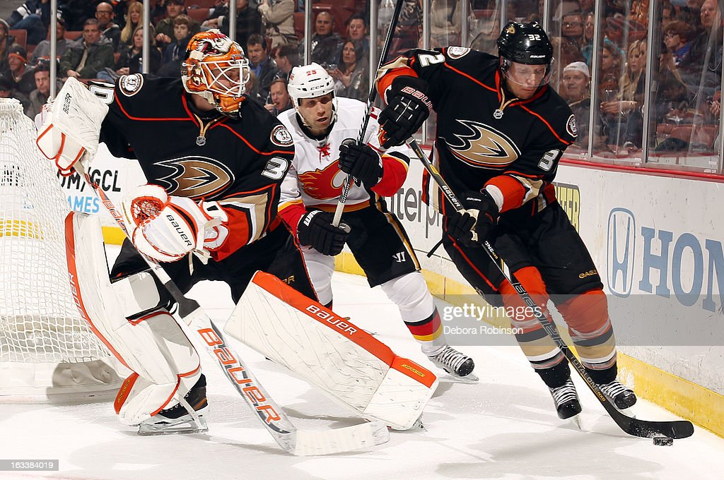 Toni Lydman #32 of the Anaheim Ducks handles the puck as teammate Viktor Fasth #30 and Paul Byron #32 of the Calgary Flames look on during the game on March 8, 2013 at Honda Center in Anaheim, California.
