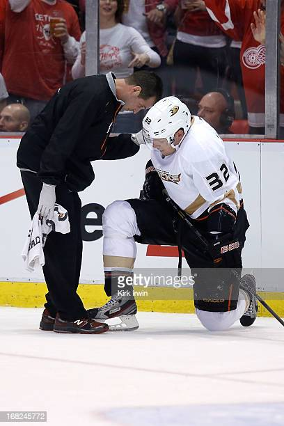 Toni Lydman of the Anaheim Ducks is looked at by a trainer after being checked by Justin Abdelkader of the Detroit Red Wings during Game Three of the...