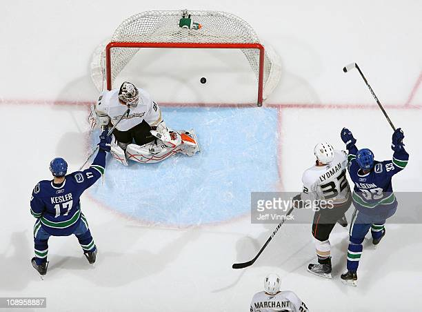 Toni Lydman of the Anaheim Ducks looks on as Ryan Kesler and Henrik Sedin of the Vancouver Canucks celebrate their goal on Curtis McElhinney of the...
