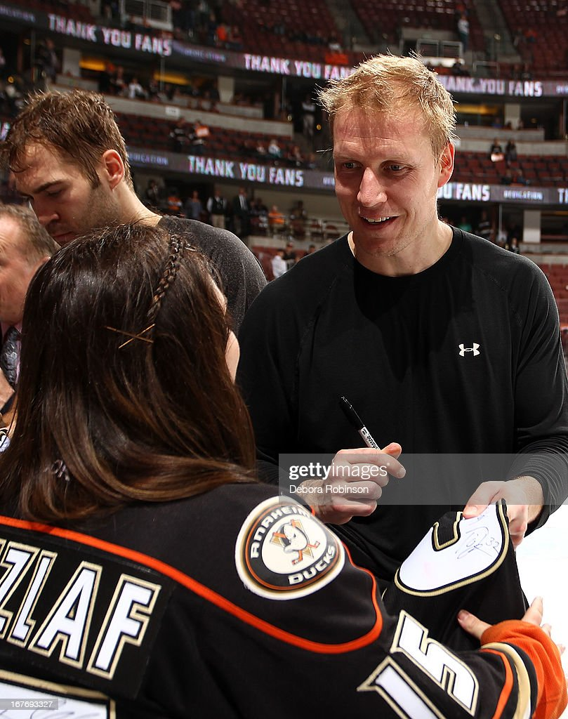 Toni Lydman #32 of the Anaheim Ducks signs his jersey for a fan for the Shirt-off-their-back for Fan Appreciation Night after the game against the Phoenix Coyotes on April 27, 2013 at Honda Center in Anaheim, California.