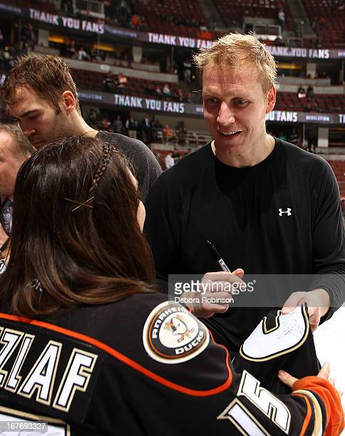 Toni Lydman of the Anaheim Ducks signs his jersey for a fan for the Shirtofftheirback for Fan Appreciation Night after the game against the Phoenix...