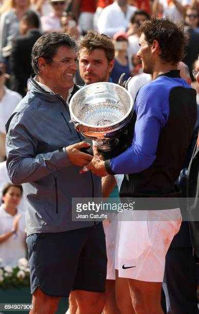 Toni Nadal and winner Rafael Nadal of Spain while finalist Stan Wawrinka of Switzerland looks on during the trophy ceremony following the men's final...