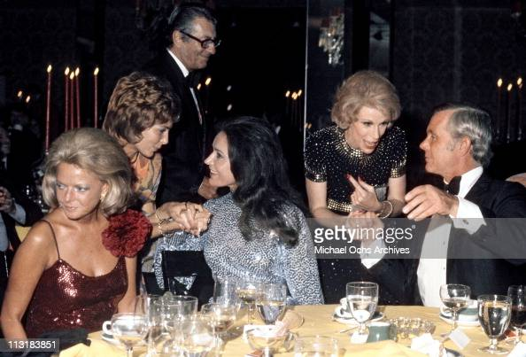 Tonight Show host Johnny Carson chats with comedienne Joan Rivers while his wife Joanna Carson talks to friends and producer Fred de Cordova walks...