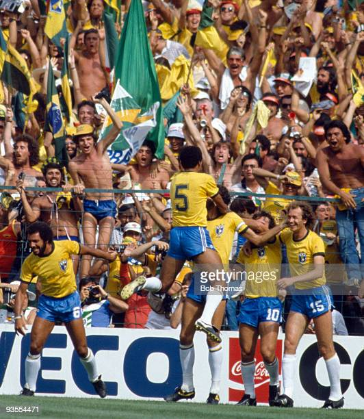 Toninho Cerezo of Brazil jumps onto goal scorer Socrates as the team celebrate in front of their fans during the Italy v Brazil World Cup match...