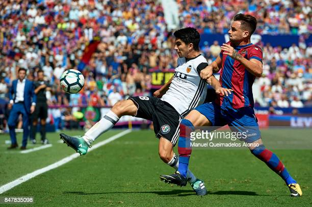 Tono Garcia of Levante competes for the ball with Carlos Soler of Valencia during the La Liga match between Levante and Valencia at Ciutat de Levante...