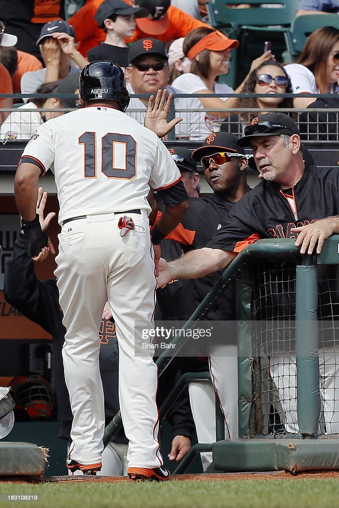 Tony Abreau #10 of the San Francisco Giants gets congratulated by manager Bruce Bochy after scoring a run against the San Diego Padres in the first inning at AT&T Park on September 29, 2013 in San Francisco, California. The Giants won 7-6 with a walk-off RBI single in the ninth inning.