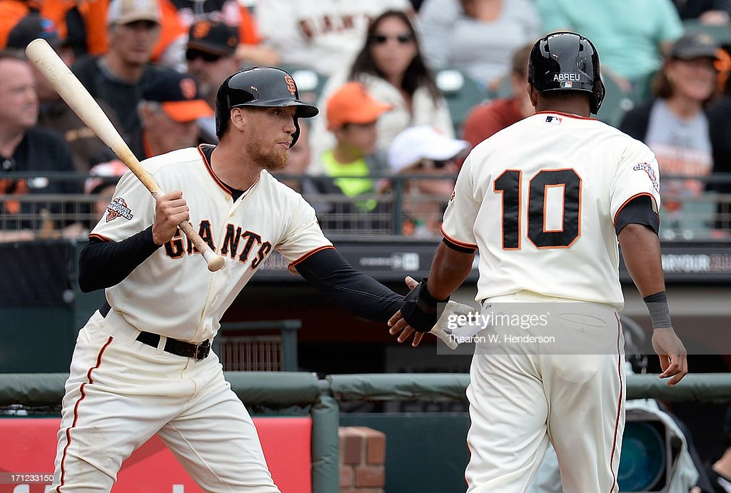 Tony Abreu #10 of the San Francisco Giants is congratulated by Hunter Pence #8 after Abreu scored in the sixth inning against the Miami Marlins at AT&T Park on June 23, 2013 in San Francisco, California.