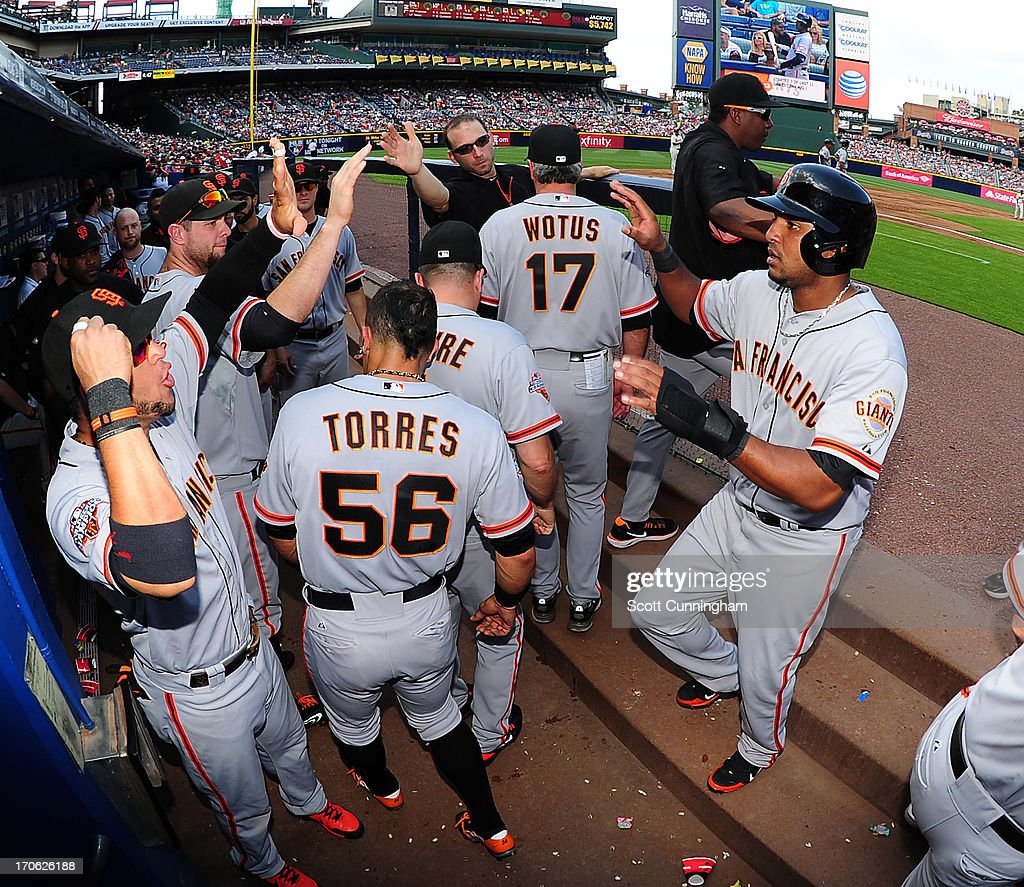 Tony Abreu #10 of the San Francisco Giants is congratulated by teammates after scoring against the Atlanta Braves at Turner Field on June 15, 2013 in Atlanta, Georgia.