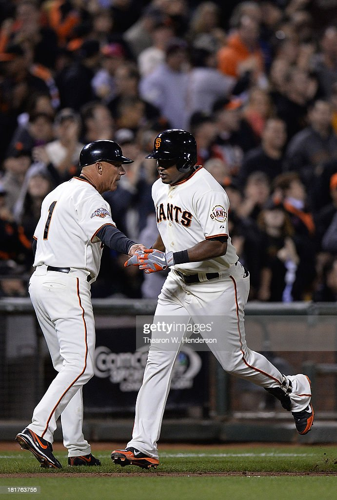 Tony Abreu #10 of the San Francisco Giants is congratulated by third base coach Tim Flannery #1 after Abreu hit a solo home run during the fifth inning against the Los Angeles Dodgers at AT&T Park on September 24, 2013 in San Francisco, California.
