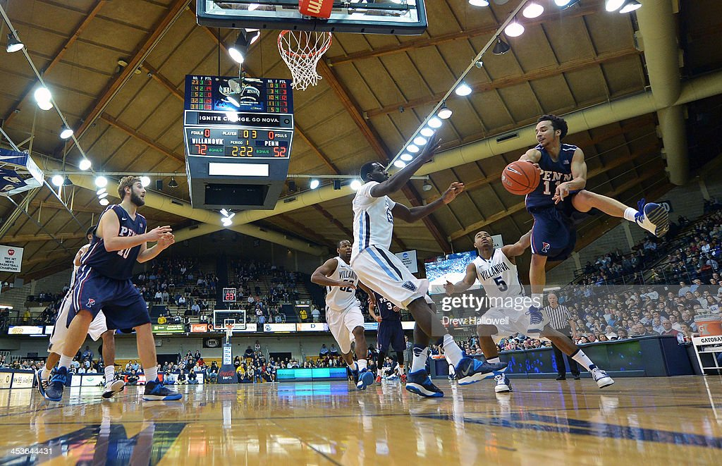 Tony Bagtas #11 of the Pennsylvania Quakers dishes off a pass to Darien Nelson-Henry #10 against the Villanova Wildcats at the Pavilion on December 4, 2013 in Villanova, Pennsylvania. Villanova won 77-54.