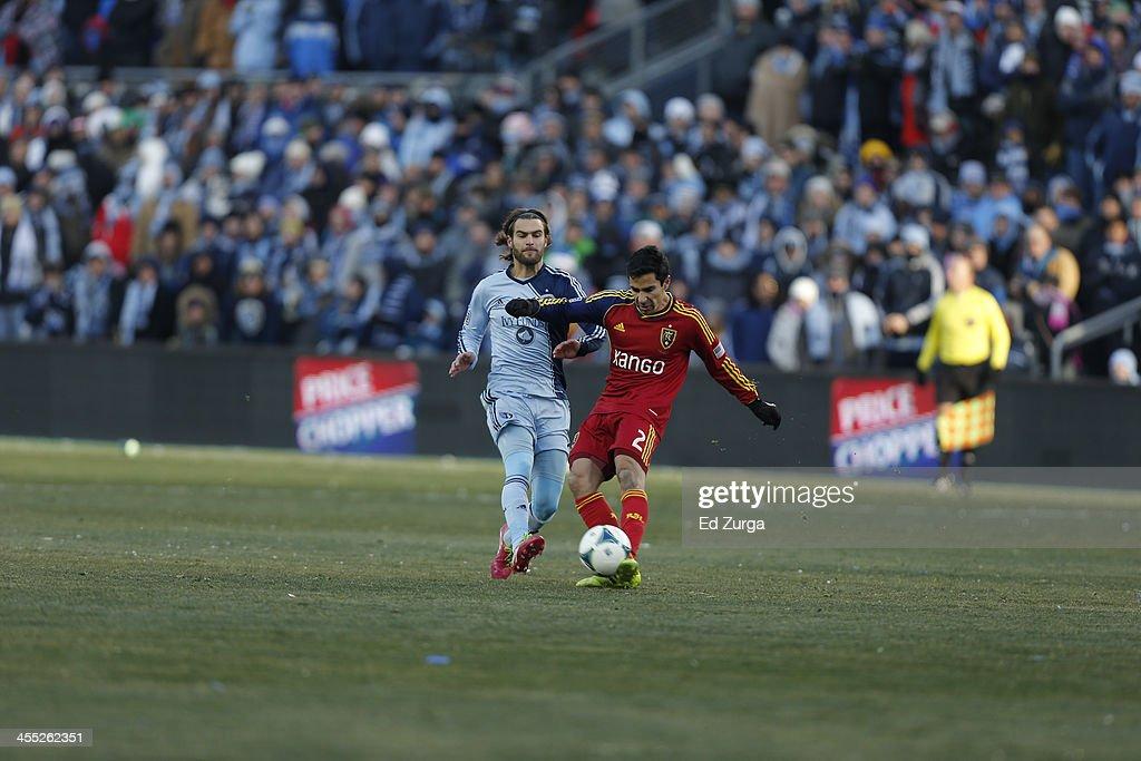Tony Beltran of Real Salt Lake kicks the ball away from Graham Zusi of Sporting Kansas City during the MLS Cup Final at Sporting Park on December 7...