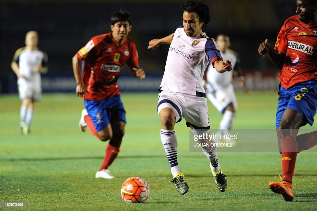 Tony Beltran (C) of US Real Salt Lake team fights for the ball with Dennis Lopez of Municipal from Guatemala during a CONCACAF Champions League football match at Mateo Flores Stadium in Guatemala City on August 4, 2015. AFP PHOTO / Johan ORDONEZ