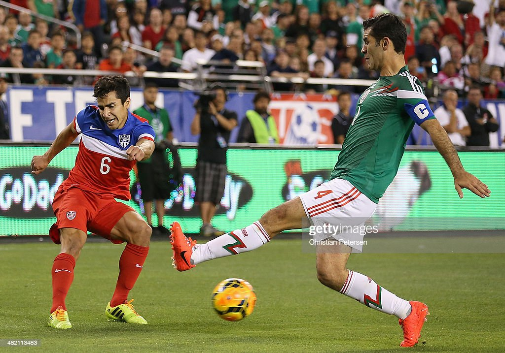 Tony Beltran of USA shoots the ball past Rafael Marquez of Mexico during the first half of the International Friendly at University of Phoenix...